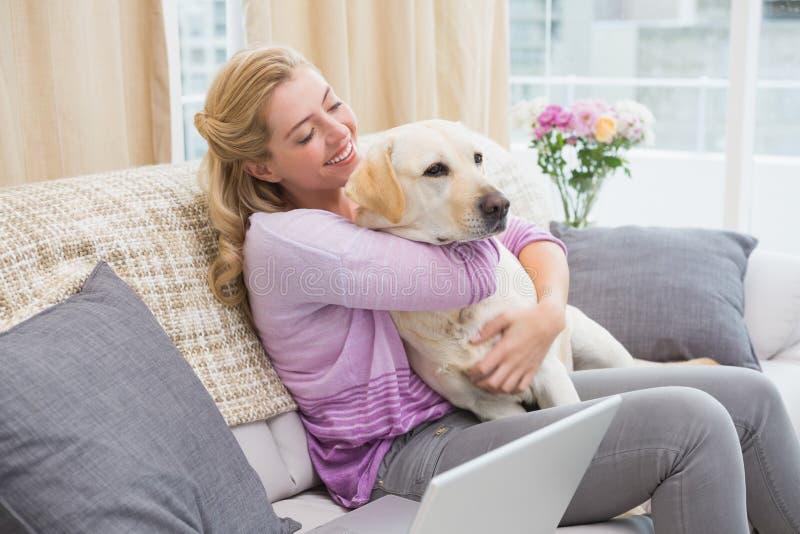 Het mooie blonde ontspannen op de laag met huisdierenhond stock afbeeldingen