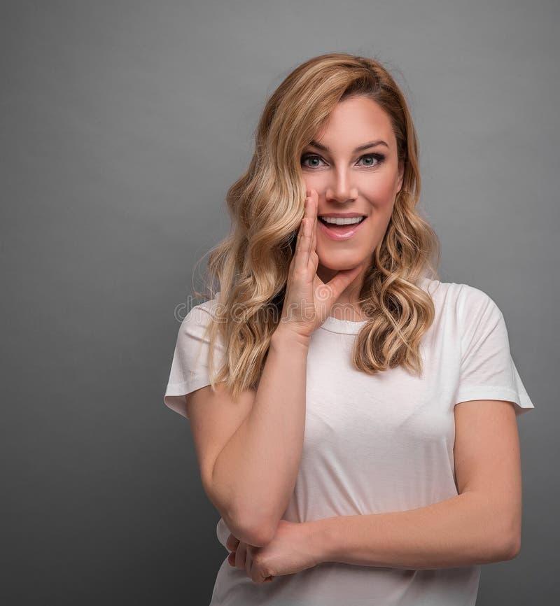 Het mooie blonde spreekt over iets die in het geheim op grijze achtergrond stellen royalty-vrije stock foto's