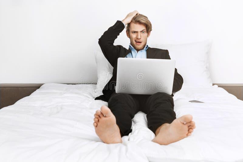 Het mooie blonde unshaved zakenman liggend in bed, die aan laptop computer werken, houdend hand op hoofd met geschokt stock foto