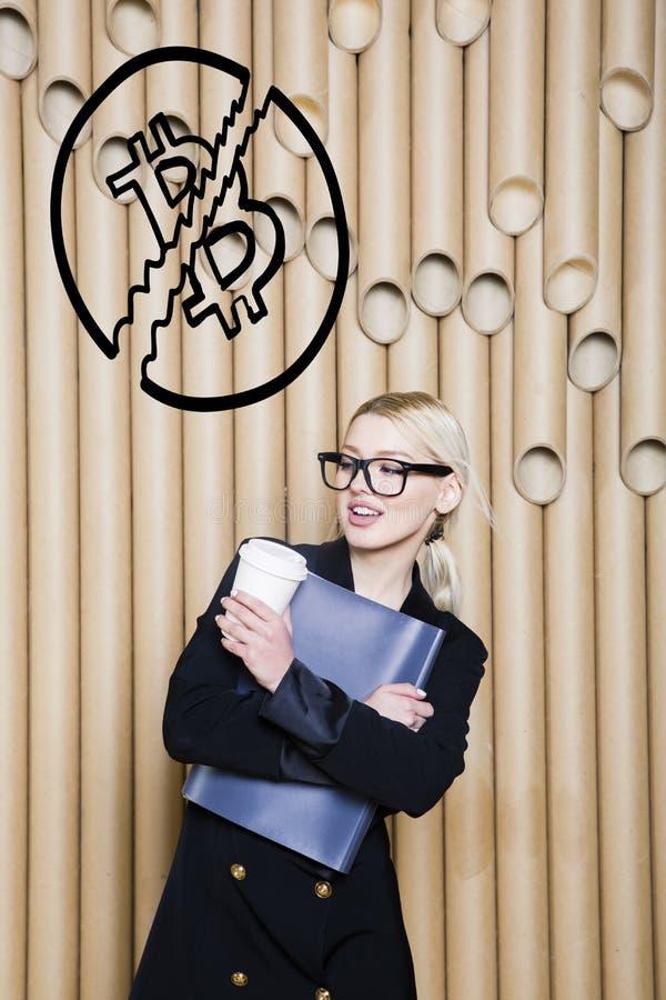 Het mooie blonde vrouw tonen die zich dichtbij bitcoin schets bevinden Virtueel geld of btc verbrijzelingsconcept Cryptocurrency stock afbeelding