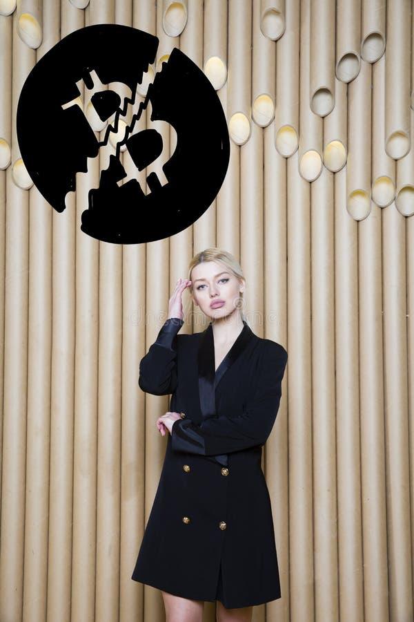 Het mooie blonde vrouw tonen die zich dichtbij bitcoin schets bevinden Virtueel geld of btc verbrijzelingsconcept Cryptocurrency royalty-vrije stock afbeelding