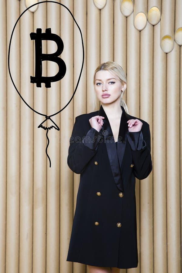 Het mooie blonde vrouw tonen die zich dichtbij bitcoin schets bevinden Virtueel geld of btc verbrijzelingsconcept Cryptocurrency stock fotografie