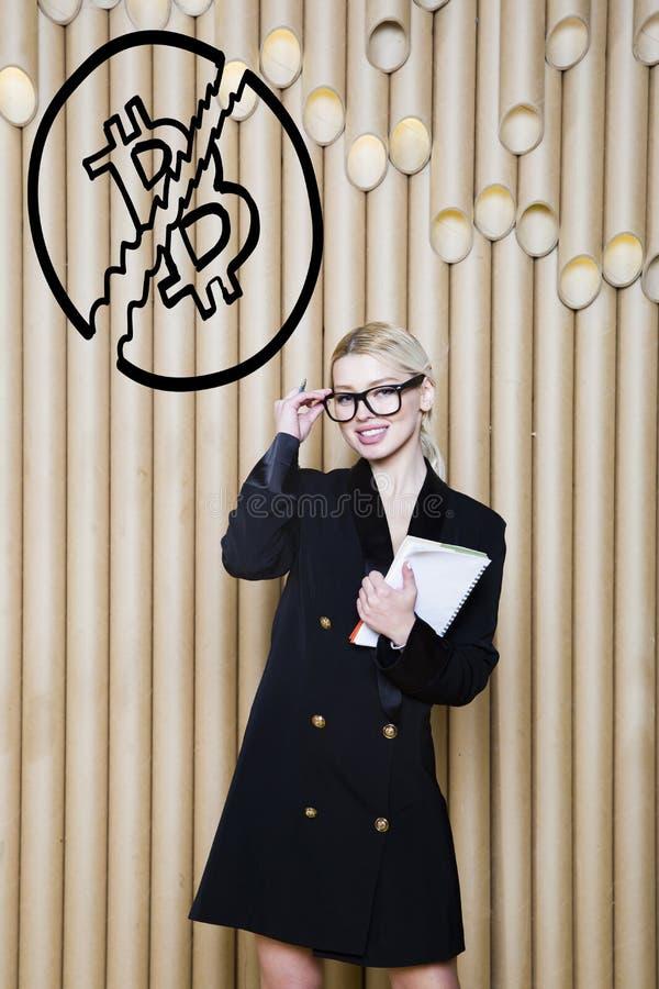 Het mooie blonde vrouw tonen die zich dichtbij bitcoin schets bevinden Virtueel geld of btc verbrijzelingsconcept Cryptocurrency royalty-vrije stock fotografie