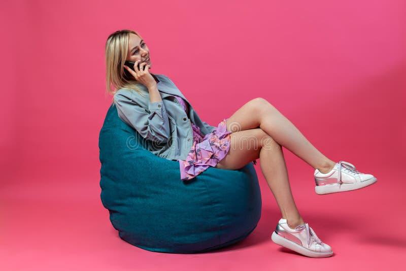 Het mooie blondemeisje in een matroos en purpere sundress zit op een groene zakstoel met haar die benen op een roze worden gevouw stock foto
