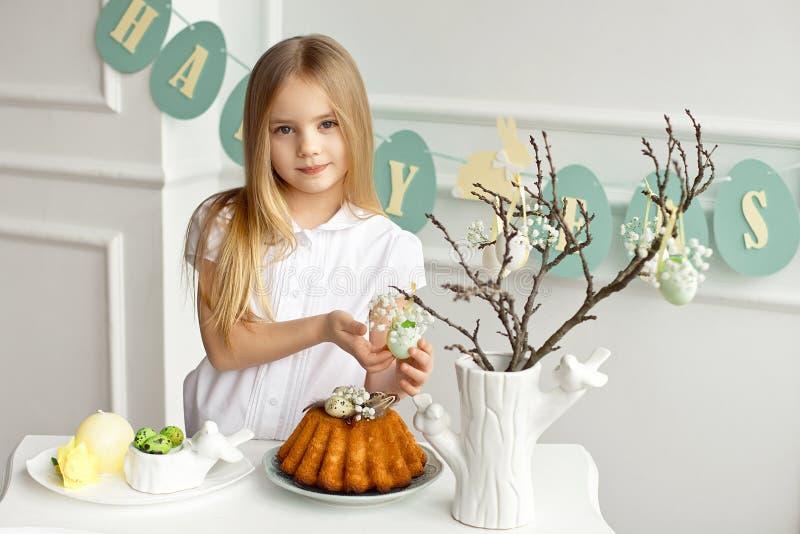Het mooie blondemeisje in een wit die overhemd zit bij de vakantielijst dichtbij een vaas met twijgen worden verfraaid met stock foto's