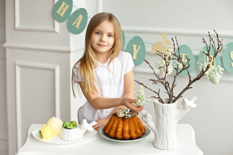 Het mooie blondemeisje in een wit die overhemd zit bij de vakantielijst dichtbij een vaas met twijgen worden verfraaid met royalty-vrije stock afbeelding