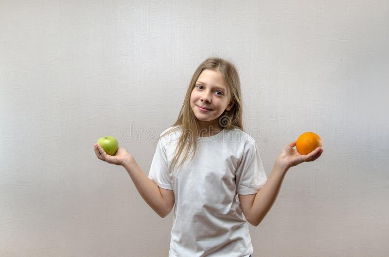 Het mooie blondemeisje in een witte T-shirt glimlacht en houdt een appel en een sinaasappel in haar handen Gezonde voeding voor stock foto's