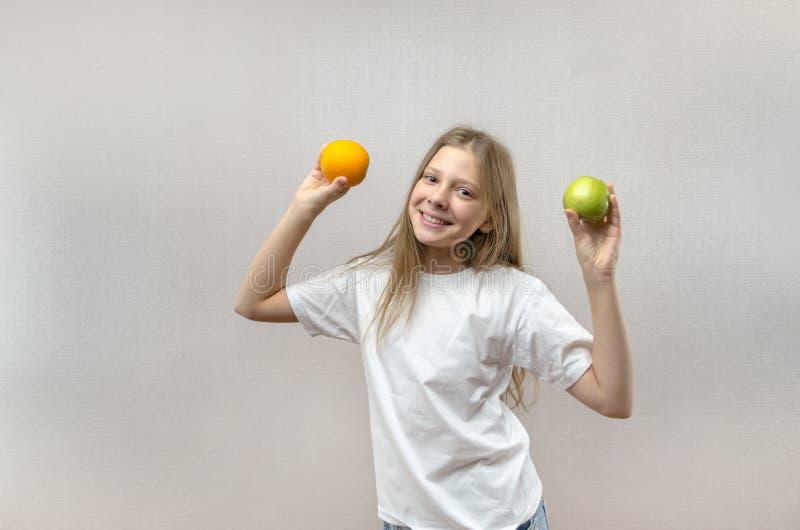 Het mooie blondemeisje in een witte T-shirt glimlacht en houdt een appel en een sinaasappel in haar handen Gezonde voeding voor royalty-vrije stock foto
