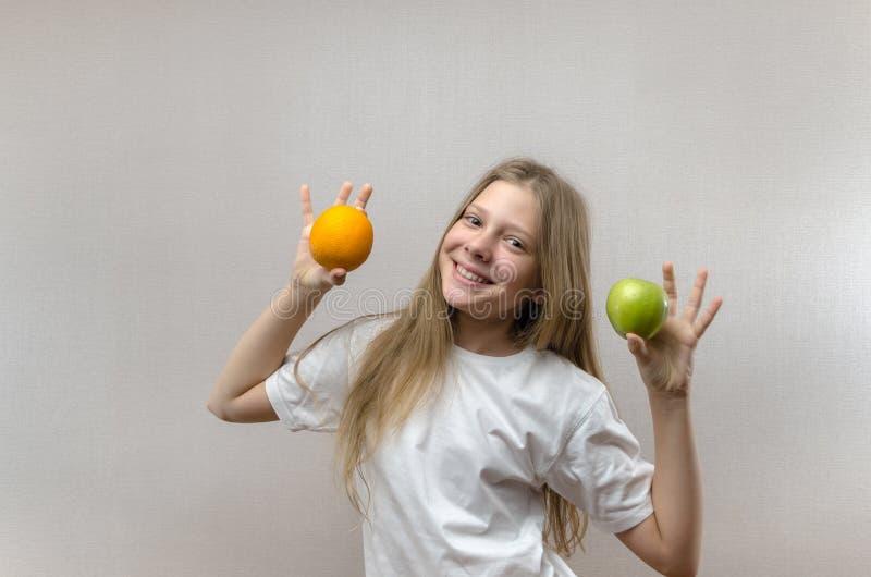 Het mooie blondemeisje in een witte T-shirt glimlacht en houdt een appel en een sinaasappel in haar handen Gezonde voeding voor stock afbeelding