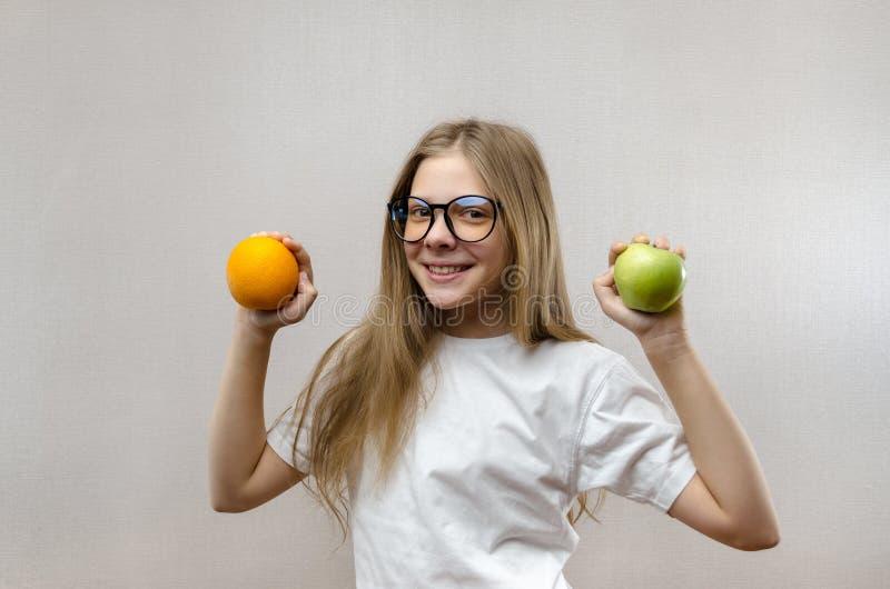 Het mooie blondemeisje in een witte T-shirt glimlacht en houdt een appel en een sinaasappel in haar handen Gezonde voeding voor royalty-vrije stock afbeelding