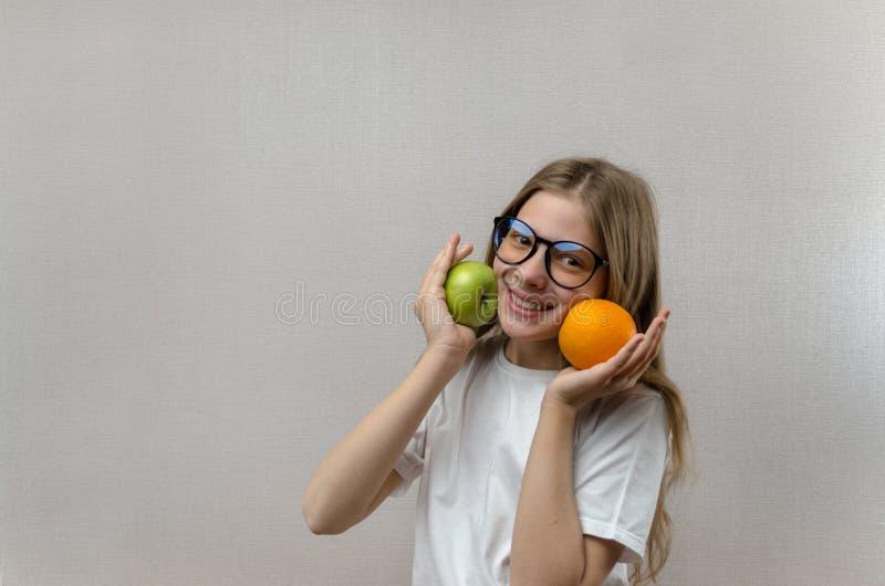 Het mooie blondemeisje in een witte T-shirt glimlacht en houdt een appel en een sinaasappel in haar handen Gezonde voeding voor royalty-vrije stock fotografie