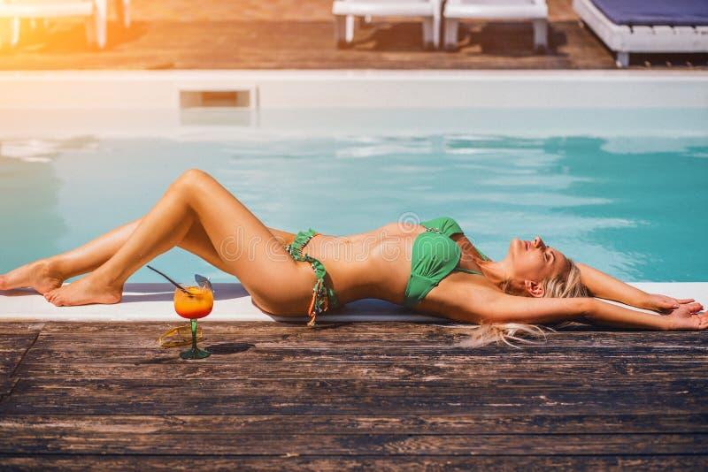 Het mooie blondemeisje in goede vorm en tan villen het liggen dichtbij het poolstrand stock foto