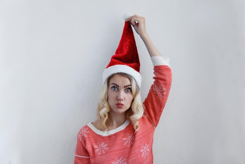 Het mooie blondemeisje in Kerstmishoed heeft pret Op een lichte achtergrond stock foto
