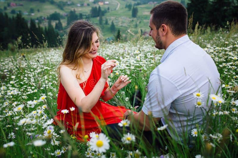 Het mooie blondemeisje met mooie glimlach en natuurlijke samenstelling speelt het spel `` hij van me, houdt van me niet `` op hou stock foto