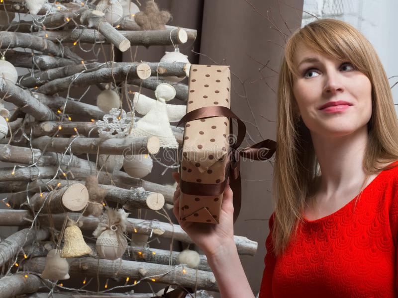 Het mooie blondemeisje in rode kleding en Nieuwjaar stelt voor Nieuwjaarstemming en binnenland stock foto's