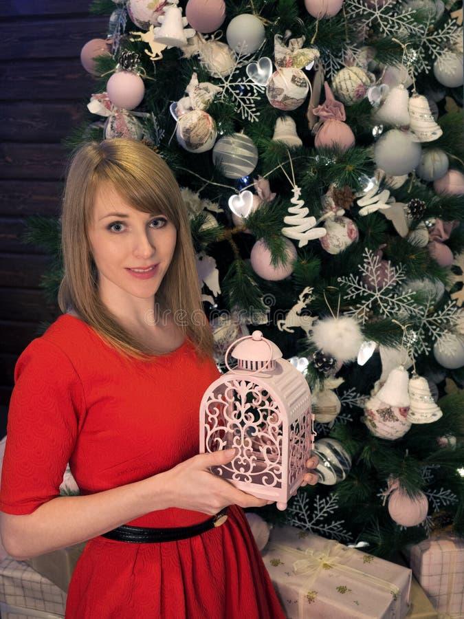 Het mooie blondemeisje in rode kleding en Nieuwjaar stelt voor Nieuwjaarstemming en binnenland royalty-vrije stock fotografie