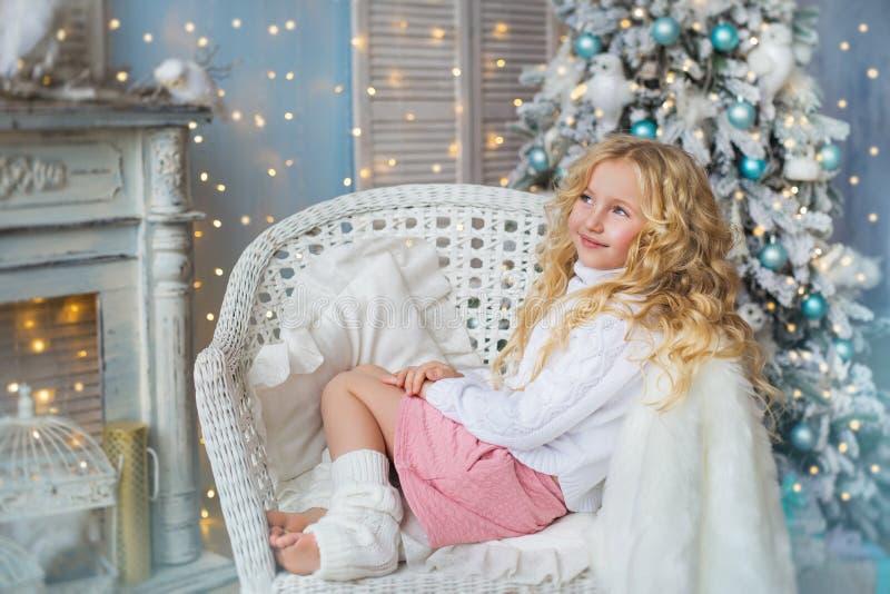 Het mooie blondemeisje zit en droomt op een stoel dichtbij een open haard en een Kerstboom stock fotografie
