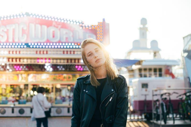 Het mooie blondemodel stelt bij pretpark stock foto's