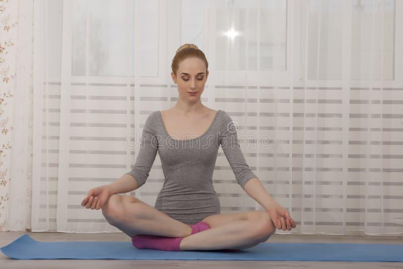 Het mooie blondevrouw het praktizeren yoga uitrekken zich thuis op blauwe mat in grijze bodysuit en roze sokken royalty-vrije stock afbeeldingen