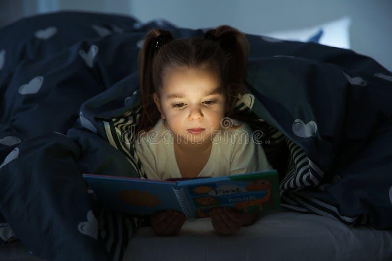 Het mooie boek van de meisjelezing in bed bij nacht stock afbeeldingen