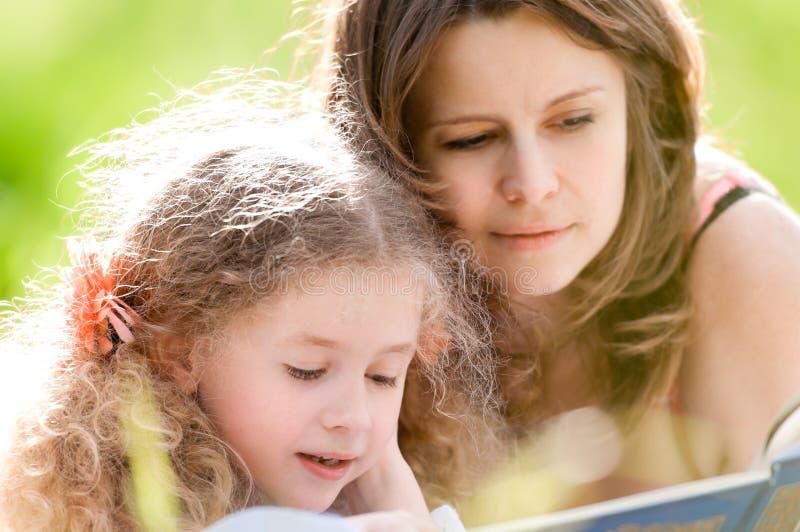 Het mooie boek van de meisjelezing met ger moeder royalty-vrije stock foto