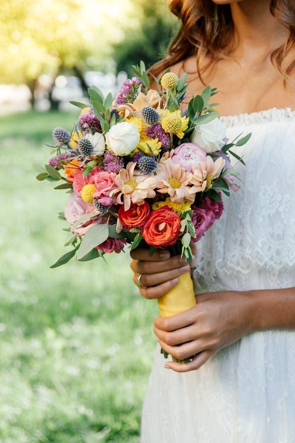 Het mooie boeket van de het huwelijksbloem van de bruidholding in handen in openlucht stock foto