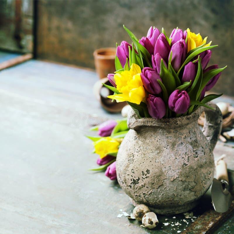 Het mooie boeket van de lentetulpen, paaseieren en tuinhulpmiddelen stock fotografie