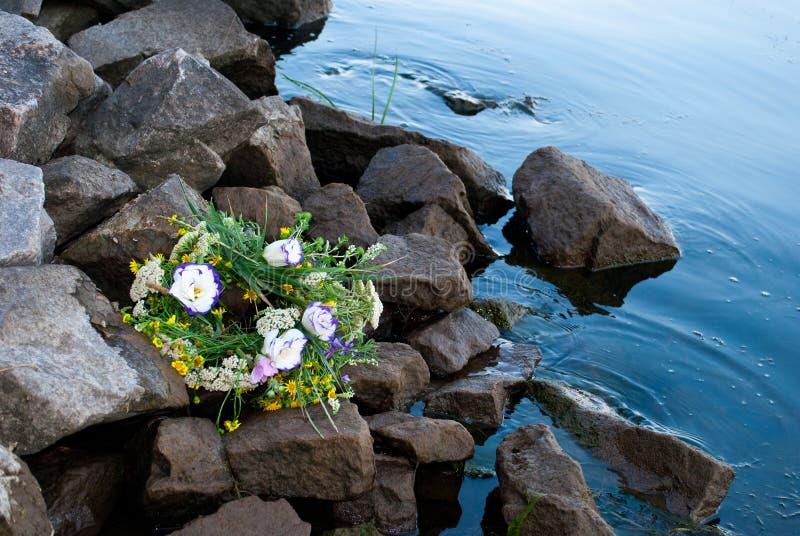 Het mooie boeket van een kroon van wildflowers ligt op de rotsen op de bank van het rivierwater royalty-vrije stock afbeeldingen
