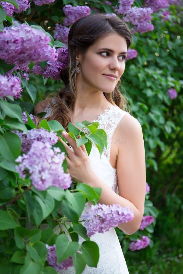 Het mooie bruid stellen dichtbij bloeiende lilac boom royalty-vrije stock fotografie