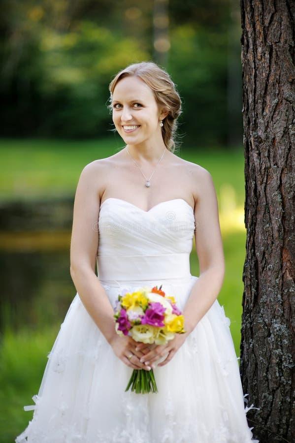 Het mooie bruid stellen in een park royalty-vrije stock foto