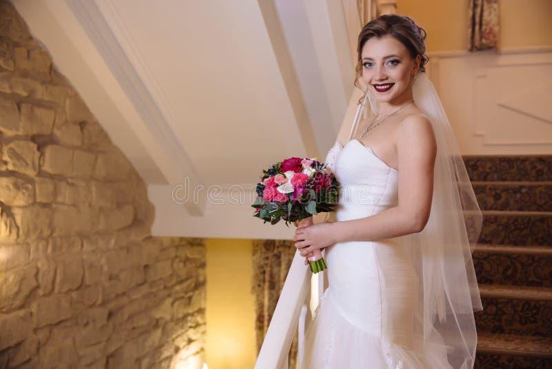 Het mooie bruid stellen met een boeket van bloemen die en zich op de treden glimlachen bevinden De Verplichte huwelijkskleding stock afbeelding