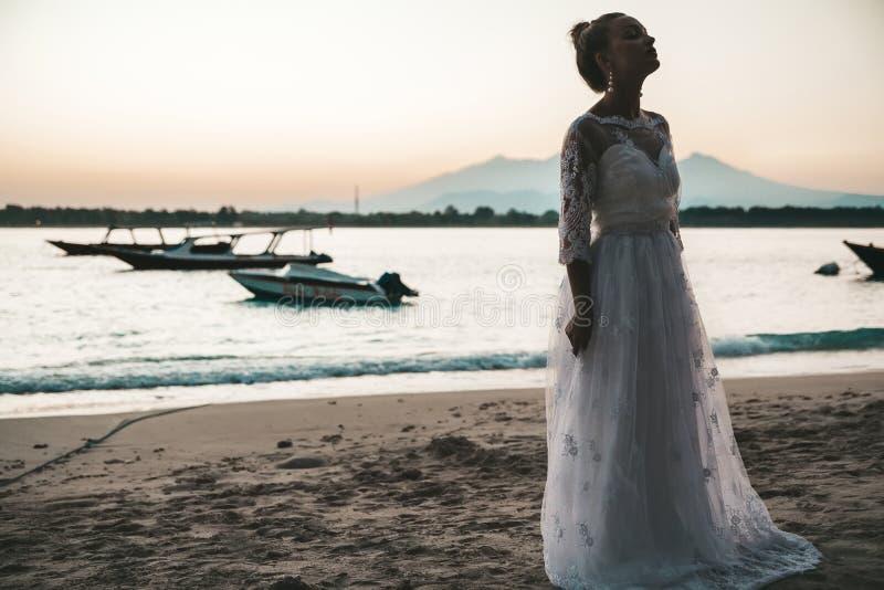 Het mooie bruid stellen op het strand achter overzees bij zonsondergang stock fotografie