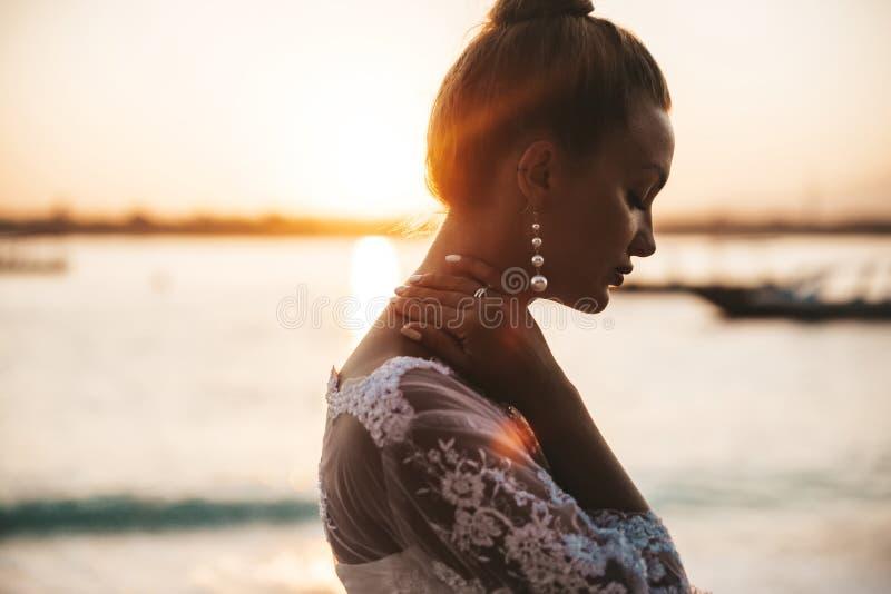 Het mooie bruid stellen op het strand achter overzees bij zonsondergang royalty-vrije stock afbeeldingen