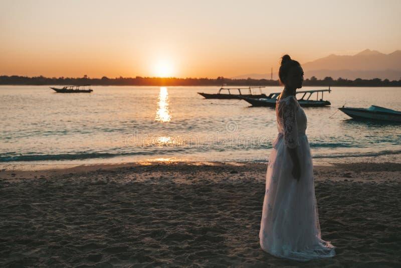 Het mooie bruid stellen op het strand achter overzees bij zonsondergang stock foto's