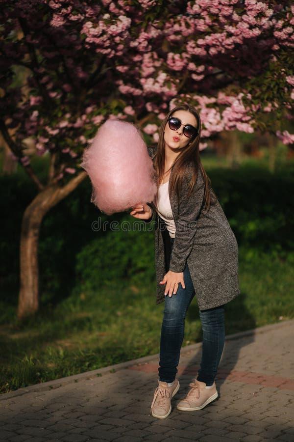 Het mooie bruine haarmodel houdt een gesponnen suiker in handen en geeft een kus Jonge vrouw met roze gesponnen suiker royalty-vrije stock afbeeldingen
