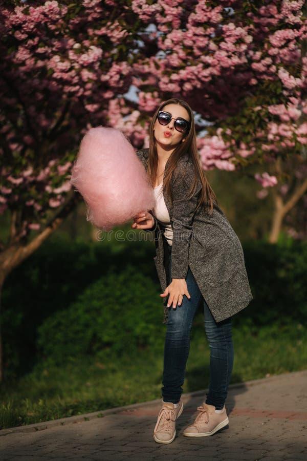 Het mooie bruine haarmodel houdt een gesponnen suiker in handen en geeft een kus Jonge vrouw met roze gesponnen suiker stock foto