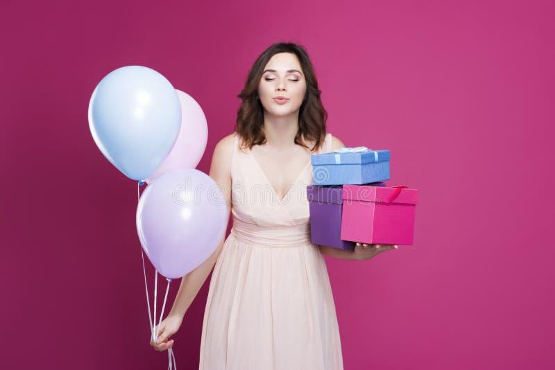 Het mooie brunette in een kleding met ogen sloot de dozen en de ballons van de holdingsgift royalty-vrije stock fotografie