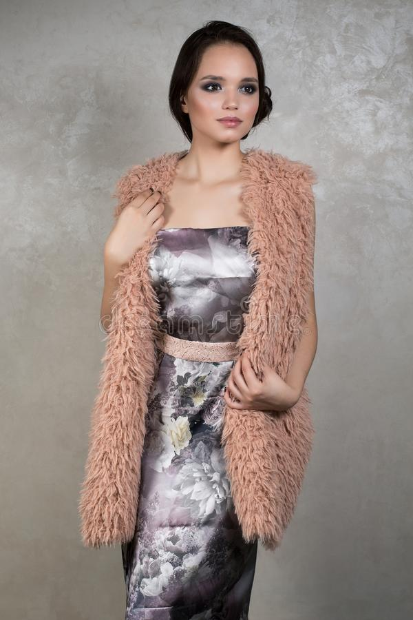 Het mooie brunette met avondmake-up in een zilveren kleding met floristical druk en beige mantel bevindt zich op een grijze achte stock foto's