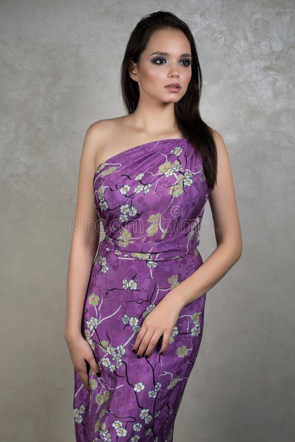 Het mooie brunette met avondmake-up in purpere kleding één schouder floristical druk is op een grijze achtergrond royalty-vrije stock afbeelding