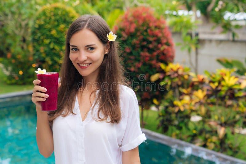 Het mooie brunette met bloem in haar haar en glazen vers sap bevindt zich in tropische tuin royalty-vrije stock foto's