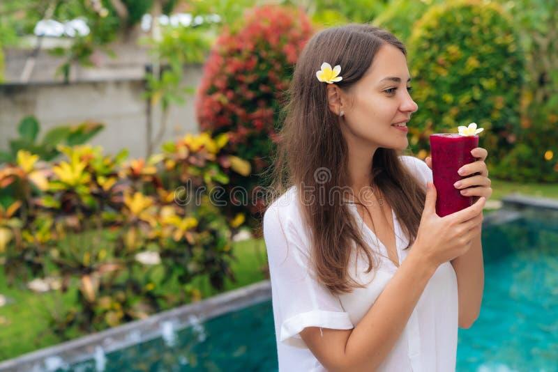 Het mooie brunette met bloem in haar haar en glazen vers sap bevindt zich in tropische tuin stock afbeelding