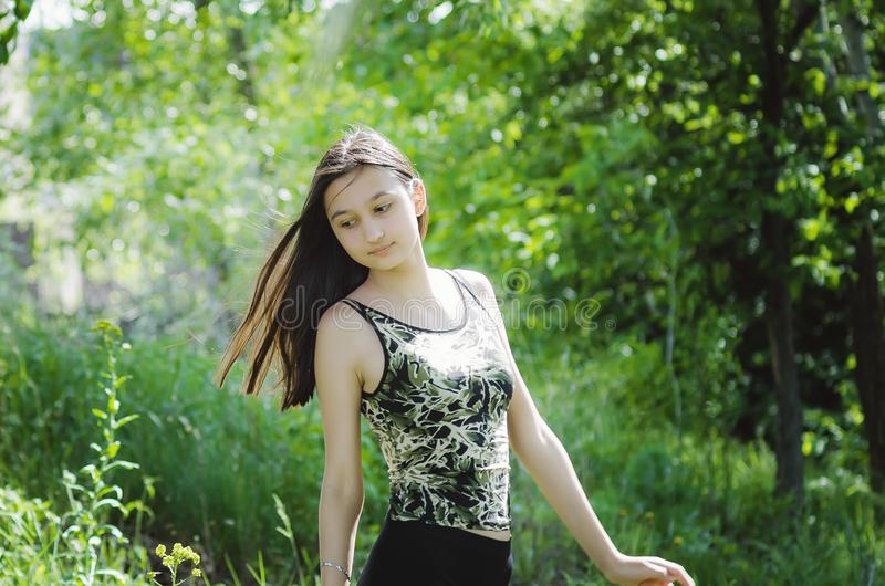 Het mooie brunette van het tienermeisje met lang haar op een achtergrond van de zomeraard stock foto