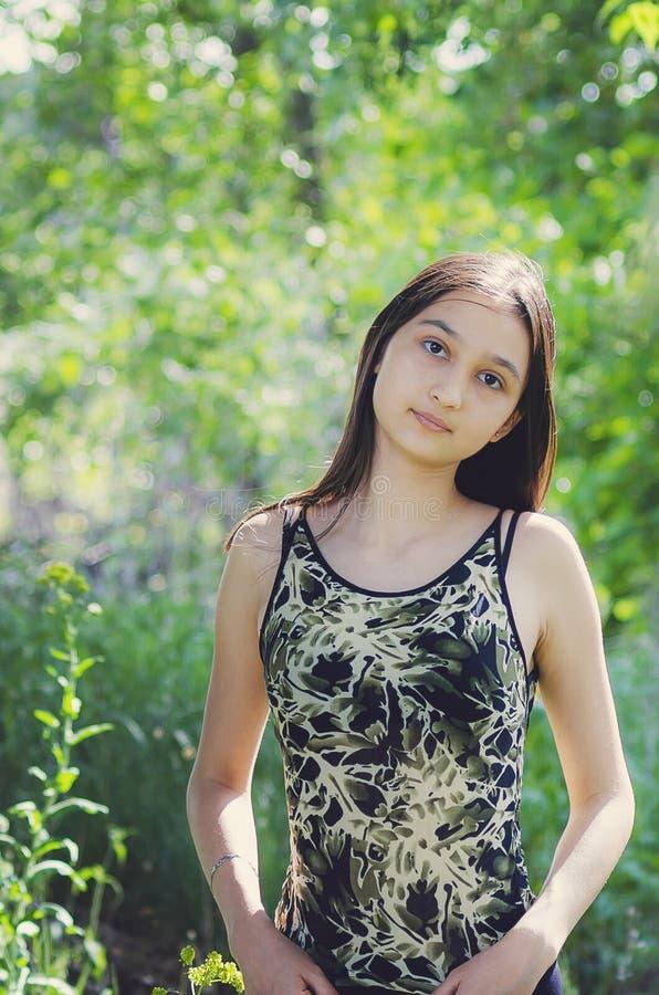 Het mooie brunette van het tienermeisje met lang haar op een achtergrond van de zomeraard Verticale Fotografie stock afbeelding
