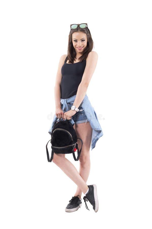 Het mooie charmante mooie meisje met modieuze pluizige zak en jeansoverhemd bond rond heupen het glimlachen royalty-vrije stock afbeeldingen