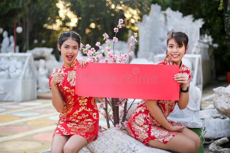 Het mooie Chinese meisje die holding dragen en toont leeg document rood, Gelukkig Chinees feestelijk Nieuwjaar en vieringsconcept royalty-vrije stock fotografie