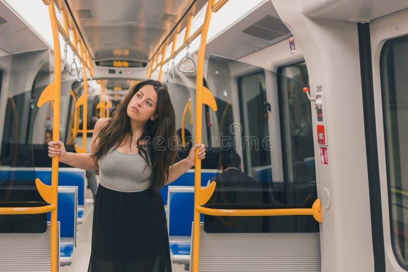 Het mooie curvy meisje stellen in een metro auto royalty-vrije stock afbeelding