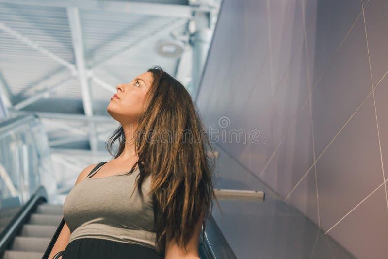Het mooie curvy meisje stellen op roltrap stock foto