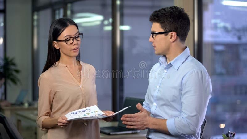 Het mooie dame chef- het controleren werk van jonge stagiair, het bekijken rapport van medewerker royalty-vrije stock afbeelding