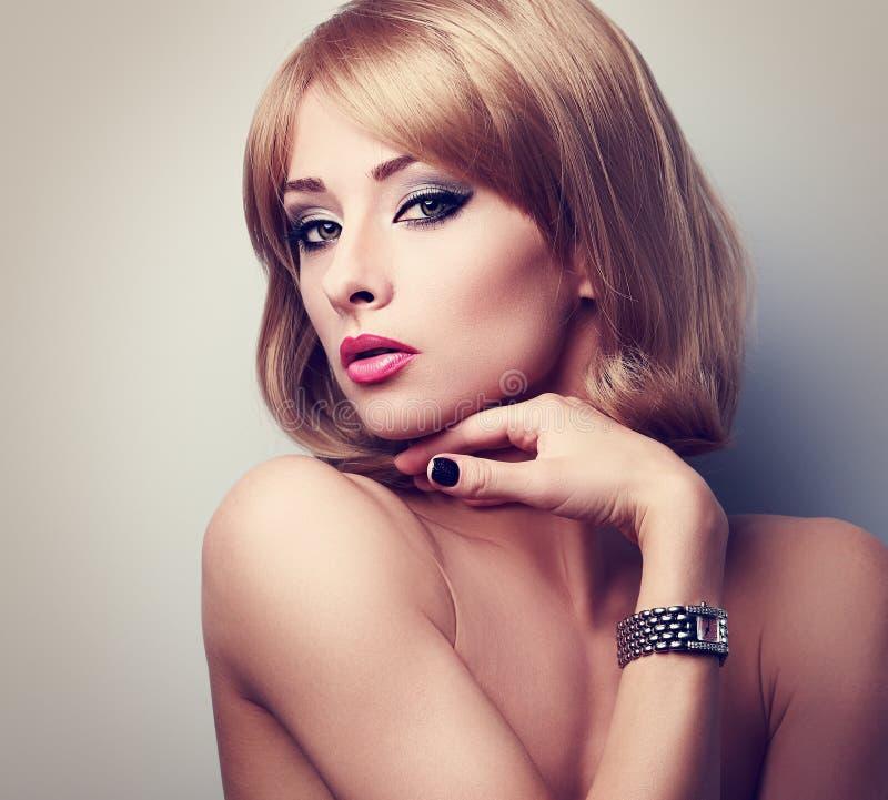 Het mooie de vrouw van de blondemake-up stellen in manierhorloges op h stock afbeeldingen