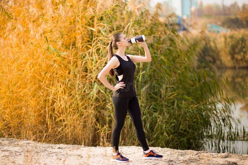 Het mooie de vrouwen drinkwater van de geschiktheidsatleet na werkt het uitoefenen op de herfstpark uit stock foto